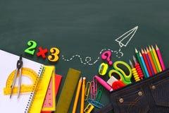Back to school concept. School supplies on blackboard. Stock Photo