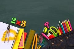 Back to school concept. School supplies on blackboard. Stock Photography