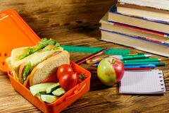 Back to school concept. School supplies, books, apple and lunch box with sandwiches and fresh vegetables on wooden desk
