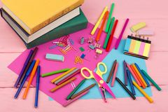 Back to school concept - school supplies: books, markers, crayons, pink and blue paper, scissors, eraser and other accessories. On pink wooden table Royalty Free Stock Photos