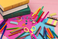 Back to school concept - school supplies: books, markers, crayons, pink and blue paper, scissors, eraser and other accessories. On pink wooden table Stock Photography