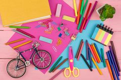 Back to school concept - school supplies: books, markers, crayons, pink and blue paper, scissors, eraser and other accessories. On pink wooden table stock photo