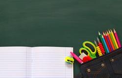 Back to school concept. School supplies on empty blackboard Stock Image