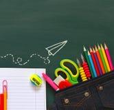 Back to school concept. School supplies on empty blackboard Stock Photo