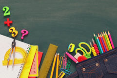 Back to school concept. School supplies on empty blackboard Royalty Free Stock Photography