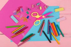Back to school concept - school supplies: markers, crayons, pink and blue paper, scissors, eraser and other accessories. On pink wooden table Stock Photography