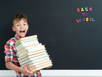 Back to school concept. Schoolboy with books at the black chalkboard in classroom Royalty Free Stock Image