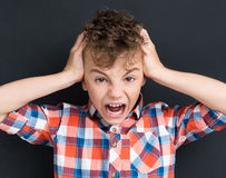 Back to school concept - shocked young boy at the black chalkboa Stock Photos
