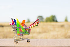 Back to school concept with shopping cart and multicolored pencils on the white background. The first of September. Royalty Free Stock Photography