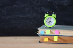 Back to school concept. stack of books and alarm clock over wooden desk in front of blackboard. stock photography