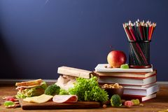 Back to School concept, school supplies, biscuits and lunchbox on wooden desk, selective focus, close-up.