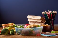 Back to School concept, school supplies, biscuits, packed lunch and lunchbox on white desk, selective focus, close-up.