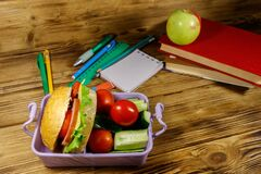 Back to school concept. School supplies, books, apple and lunch box with burgers and fresh vegetables on wooden table