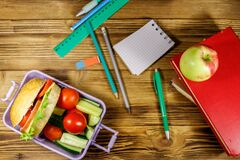 Back to school concept. School supplies, books, apple and lunch box with burgers and fresh vegetables on wooden table. Top view