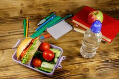 Back to school concept. School supplies, books, bottle of water, apple and lunch box with burgers and fresh vegetables