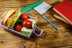 Back to school concept. School supplies, books and lunch box with burgers and fresh vegetables on wooden table