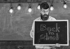Back to school concept. Teacher in eyeglasses holding chalkboard with sentence back to school written in it. Man with. Beard and mustache on surprised face stock photos