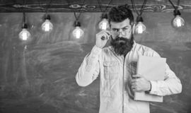 Back to school concept. Teacher in eyeglasses starting lesson. Man with beard and mustache on serious face stand in. Front of chalkboard. Bearded hipster holds stock image