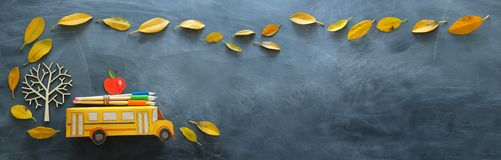 Back to school concept. Top view banner of cardboard school bus, apple and pencil next to tree with autumn dry leaves over. Classroom blackboard background royalty free stock image