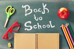 Back to school concept. Top view of school supplies on blackboar Stock Images