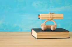 Back to school concept. Wooden toy car with colorful pencils on the roof over stack of book stock images