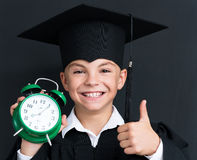 Back to school concept. Young boy Bachelor with alarm-clock looking at camera at the black chalkboard in classroom Stock Photos