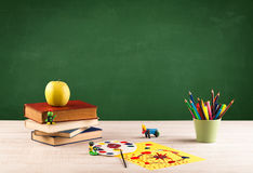 School items on desk with empty chalkboard Royalty Free Stock Photos