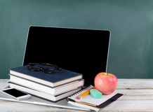 Back to school consisting of technology and traditional stationery with green chalkboard royalty free stock images