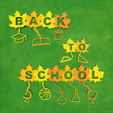 Back to school. Creative concept. Yellow and orange maple leaves with text and with stalks in the form of school supplies on blackboard background as symbol of Royalty Free Stock Image