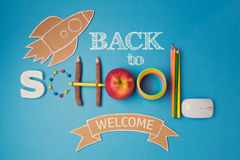 Back to school creative design with smartphone, apple, school supplies and cardboard rocket. Royalty Free Stock Photos