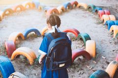 Cute asian pupil girl with backpack playing in playground Royalty Free Stock Photography