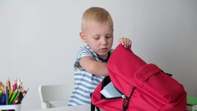 Back to school. Cute little boy putting book to his bag. Child from elementary school. stock footage