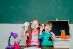 Back to school. Cute little preschool kid boy with Little child girl play with paper airplane in a classroom. Little. Ready to study royalty free stock photos