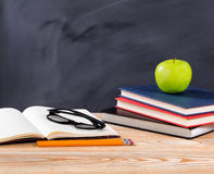 Back to school desk with stationery objects in front of erased b. Back to school concept with reading glasses, pencils, notepad, books and green apple on desktop Stock Image