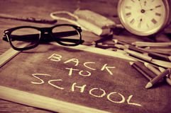 Back to school in duotone. A chalkboard with the sentence back to school written in it, on a rustic wooden desk with a pair of eyeglasses and other school royalty free stock images