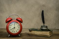 Back to school. Education background. Memoirs. Writer table concept. Old book retro red alarm clock and feather pen with inkpot and rusty key on retro wooden royalty free stock images
