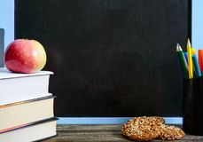 Back to school, education concept. Books, useful whole-grain cookies and apple on classroom table in front of blackboard. Back to school, education concept stock photos