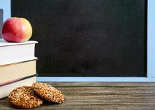 Back to school, education concept. Books, useful whole-grain cookies and apple on classroom table in front of blackboard. Copy space. You will be healthy and royalty free stock photo
