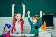 Back to school - education concept. Cheerful smiling little boy and cute little girl having fun against blackboard royalty free stock image
