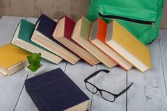 education concept - colorful hardback books, eyeglasses and green backpack on brown background royalty free stock images