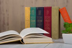 Back to school and education concept - heap hardback books on white wooden table on brown background stock photo