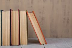 Back to school and education concept  heap colorful hardback books on white wooden table on brown background royalty free stock photography