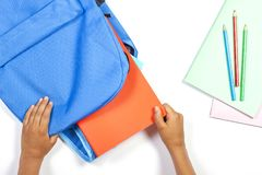 Back to school, education concept. Kid hands packing backpack and preparing for school stock image