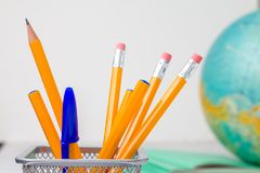 Back to school and education concept. school office supplies pencils, pens in stand, paper, notebook and globe on boke background. Back to school and education stock image