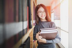 Back to school education knowledge college university concept, Beautiful female college student holding her books smiling happily. Standing in library, Learning royalty free stock photo