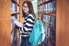 Back to school education knowledge college university concept, Beautiful female college student holding her books smiling happily. Standing in library, Learning royalty free stock photography