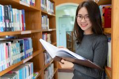 Back to school education knowledge college university concept, Beautiful female college student holding her books smiling happily. Standing in library, Learning stock images