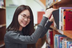 Back to school education knowledge college university concept, Beautiful female college student holding her books smiling. Happily standing in library, Learning stock photography