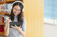 Back to school education knowledge college university concept, Female student study in library using tablet and searching internet. While Listening music and stock photography
