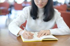 Back to school education knowledge college university concept, Young business woman sitting at table and taking notes in notebook royalty free stock image